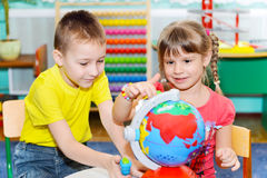 Little children study globe Royalty Free Stock Photography