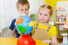 Little children study globe Stock Photo