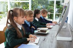 Little children in stylish school uniform at desks. With computers royalty free stock photos