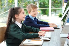 Little children in stylish school uniform. At desks with computers stock photography