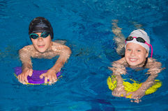 Little children swim in the poo. L under the guidance of a coach stock photography
