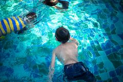 Children swimming in pool royalty free stock images