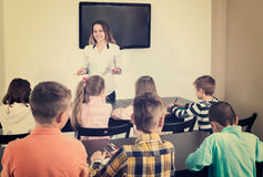 Little children with teacher in classroom. Little children with teacher in a classroom Royalty Free Stock Photos