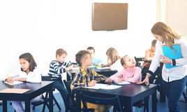 Little children with teacher in classroom. Professor and elementary age children at classroom Royalty Free Stock Images