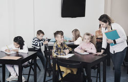 Little children with teacher in classroom. Professor and elementary age children in classroom Stock Images