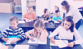 Little children with teacher in classroom. Professor and elementary age children at the classroom in a school Royalty Free Stock Photos