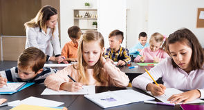 Little children with teacher in classroom. Professor and elementary age children at a classroom in the school Royalty Free Stock Image