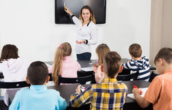 Little children with teacher in classroom. Professor and elementary age children at classroom in a school Stock Photos