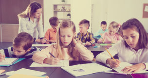 Little children with teacher in classroom. Professor and elementary age children at a classroom in the school Royalty Free Stock Photography