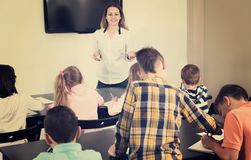 Little children with teacher in classroom. Professor and elementary age children at the classroom in school Royalty Free Stock Image
