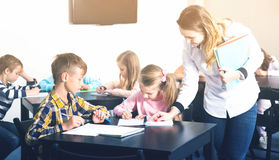 Little children with teacher in classroom. Little children with their teacher at a classroom in school Royalty Free Stock Image
