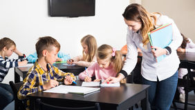 Little children with teacher in classroom. Little children with their teacher at a classroom in school royalty free stock photos