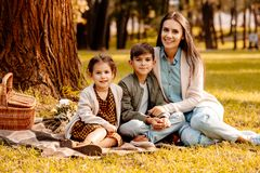 Little children and their mom sitting on a picnic blanket. In autumn park stock photo
