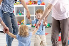 Little children and mothers roundelay in daycare royalty free stock photography
