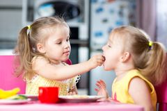 Little children toddlers eating meal together, one girl feeding sister in sunny kitchen at home. Two little children toddlers eating meal together, one girl Royalty Free Stock Photos
