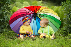 Little children under colorful umbrella Stock Image