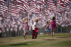 Little children walk beneath display of USA Flags Stock Images