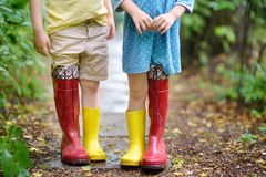 Little children wearing oversized rubber boots holding hands. Brother and sister playing together royalty free stock photo