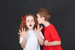Little children whispers near school board. Stock Photos