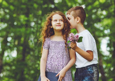 Little children whispers in spring park. Royalty Free Stock Photography