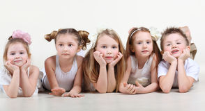 Little children in white clothes lie on floor. Five cute little children in white clothes lie on floor and look at camera stock photography