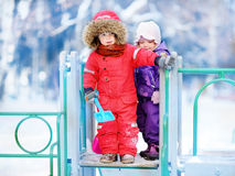 Little children in winter clothes having fun on playground at the snowy winter day Stock Photos