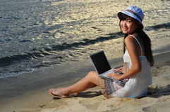 Little Chinese Asian girl on beach with laptop. Little Chinese Asian Tourist Girl enjoying her holiday under the sun royalty free stock photography