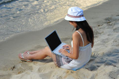 Little Chinese Asian girl on beach with laptop Stock Photography