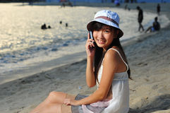Little Chinese Asian girl on beach with phone Royalty Free Stock Images