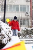 A little Chinese boy in red holding two balloons is playing in the snow Royalty Free Stock Image