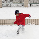 A little Chinese boy in red is playing in the snow Stock Photo