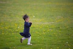 Happy gril running on dandelion field