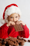 Little chocolate Santa. Little girl wearing red Santa hat eating chocolate Royalty Free Stock Photography