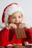 Little chocolate Santa. Little girl wearing red Santa hat eating chocolate Royalty Free Stock Photos