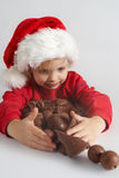 Little chocolate Santa. Little girl wearing red Santa hat eating chocolate Stock Images