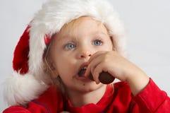 Little chocolate Santa. Little girl wearing red Santa hat eating chocolate Stock Photo