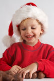 Little chocolate Santa. Little girl wearing red Santa hat eating chocolate Stock Photography