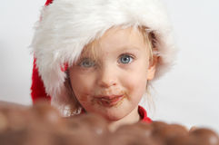 Little chocolate Santa. Little girl wearing red Santa hat eating chocolate Royalty Free Stock Images