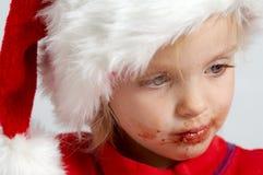 Little chocolate Santa. Little girl wearing red Santa hat eating chocolate Royalty Free Stock Photo