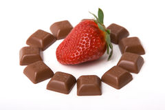 Little chocolate and strawberry. A fresh red strawberry surrounded by little chocolate bars Royalty Free Stock Photos