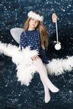 Little christmas angel. Little girl as angel holding Christmas ornament on night sky background Stock Photos