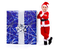 Little Christmas boy next to big gift Royalty Free Stock Photos