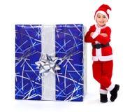 Little Christmas boy next to big gift Royalty Free Stock Photos