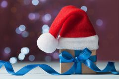 Little christmas gift box or present and santa hat against magic bokeh background. Holiday greeting card. Royalty Free Stock Photography