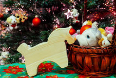 Little Christmas horse. A wooden toy horse near the festive Christmas tree, along with a basket of toys Stock Image
