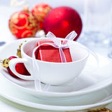 Little christmas present in a white coffee cup. Red christmas present in a white coffee cup Royalty Free Stock Photography