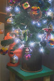 Little Christmas tree decorated with vintage toys. Stands on the stool. The garlands are sparkling in the dark. Vintage rustic style, soft focus Stock Images