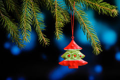 Little Christmas tree toy, on pine branch on blue bokeh bacground.  Royalty Free Stock Image