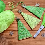 Little Christmas trees are made of carton, cotton yarn and decorated with small metal snowflakes. Easy and cheap Christmas crafts Stock Photography