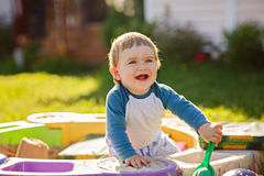 Little chubby baby boy laughs, sitting in the sandbox in the sum Stock Images